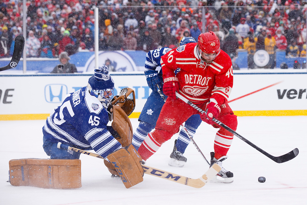 Jan 1, 2014; Ann Arbor, MI, USA; Toronto Maple Leafs goalie Jonathan Bernier (45) makes a save on Detroit Red Wings left wing Henrik Zetterberg (40) during the 2014 Winter Classic hockey game at Michigan Stadium. Mandatory Credit: Rick Osentoski-USA TODAY Sports