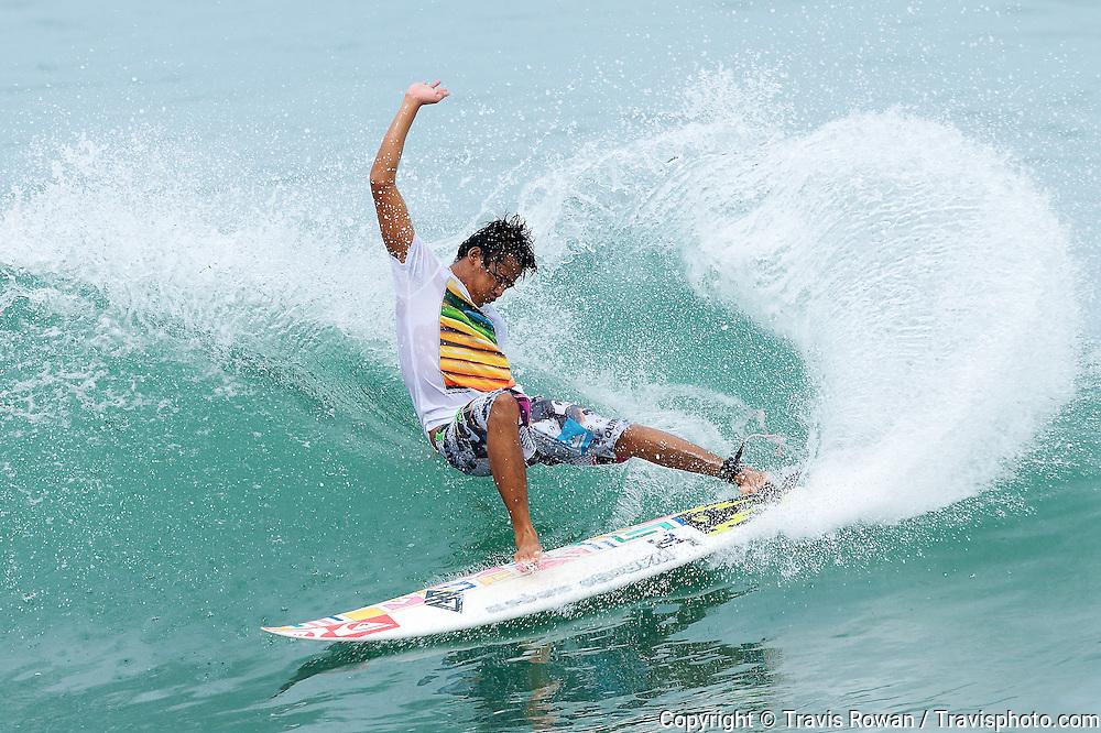 Professional Balinese surfer, Mustofa Jeksen in action on Canggu beach, Bali.