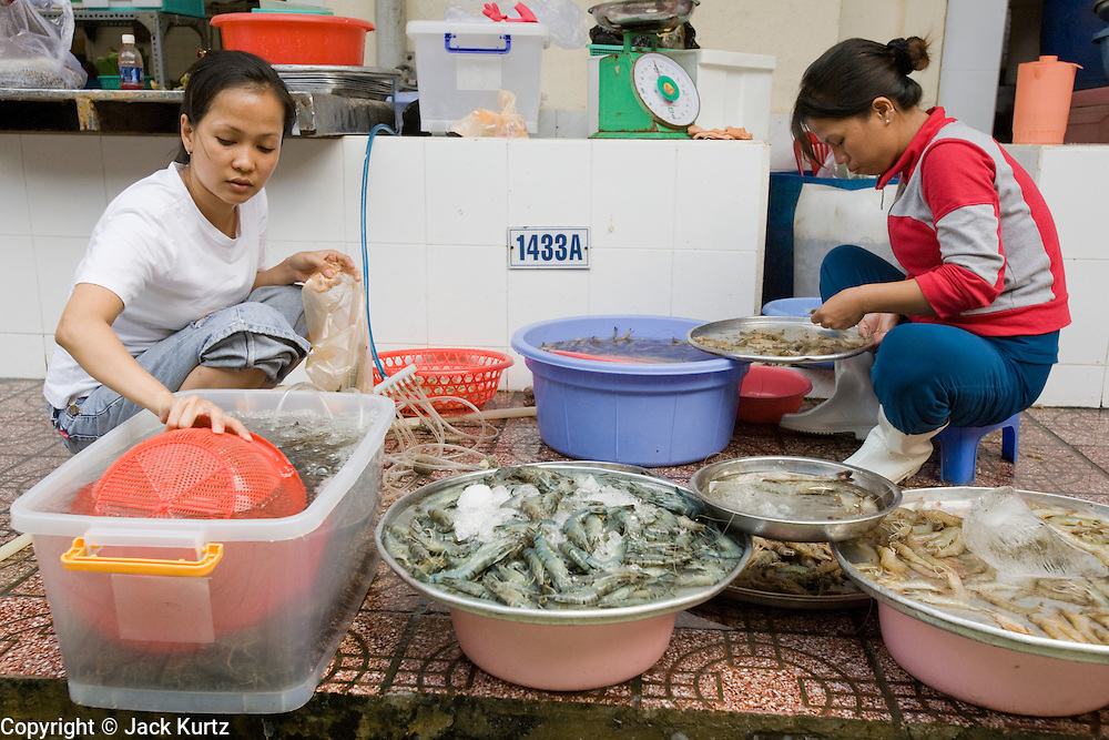 09 MARCH 2006 - HO CHI MINH CITY, VIETNAM: Women in the main market in Ho Chi Minh City (Saigon), Vietnam clean shrimp and sort shrimp before putting them on sale. Many people in developing countries, like Vietnam, shop everyday for fresh food because many families don't have the large refrigerators families in the US do. PHOTO BY JACK KURTZ
