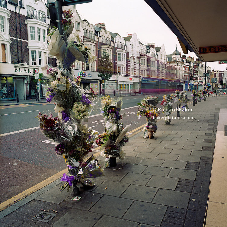 Memorials have been placed where a young man called 'Marurice' died on the A215 Walworth Road in London, England, UK. Were we to ignore this place where someone's life ended, the victim would just be an anonymous statistic but flowers are left to die too and touching poems and dedications are written by family and loved-ones. One read: ?Top fella/Don't worry, I'll look after your sisters/May you and your family find true justive so your soul may rest in Peace.? From a project about makeshift shrines: Britons have long installed memorials in the landscape: Statues and monuments to war heroes, Princesses and the socially privileged. But nowadays we lay wreaths to those who die suddenly - ordinary folk killed as pedestrians, as drivers or by alcohol, all celebrated on our roadsides and in cities with simple, haunting roadside remberences.