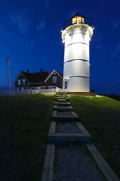 New England photography of Nobska Lighthouse at twilight. This iconic Massachusetts lighthouse is located near Woods Hole Village in Falmouth, MA on Cape Cod.<br />