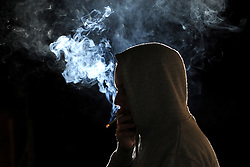 A silhouetted man smokes a cigarette. <br />