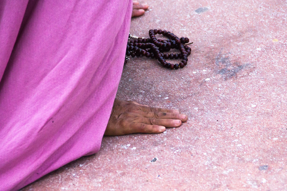 The hands of a devote buddhist woman, during her morning prayers at the stupa of Bodnath, Nepal.