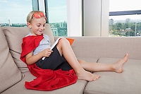 Smiling boy in superhero costume reading book on sofa at home