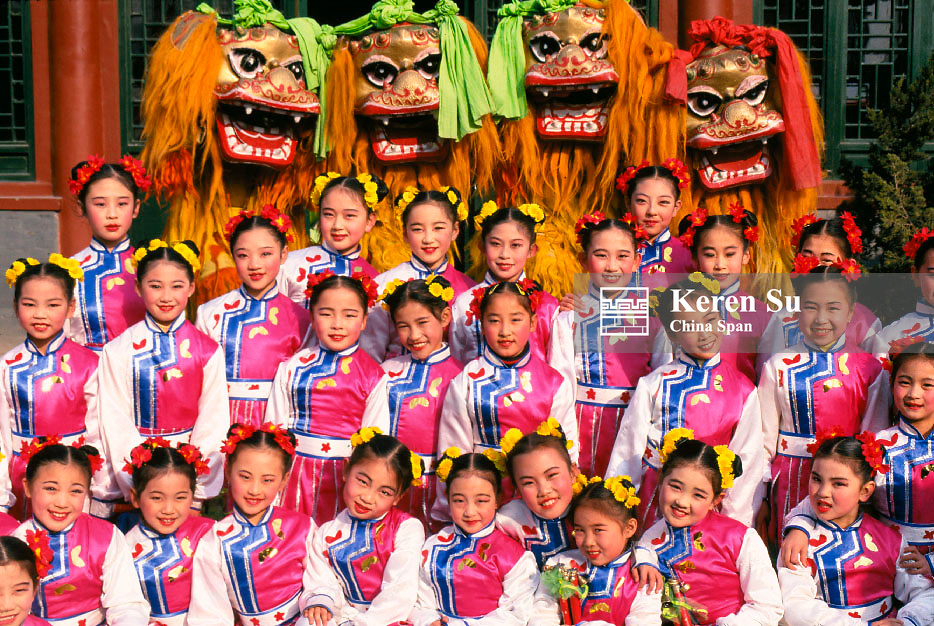 Chinese girls in costume with lion dance performers celebrating Chinese New Year, China