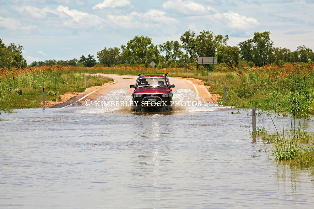 A car fords a small creek crossing on the road from the Broome highway down to Fitzroy Crossing after wet season rain.