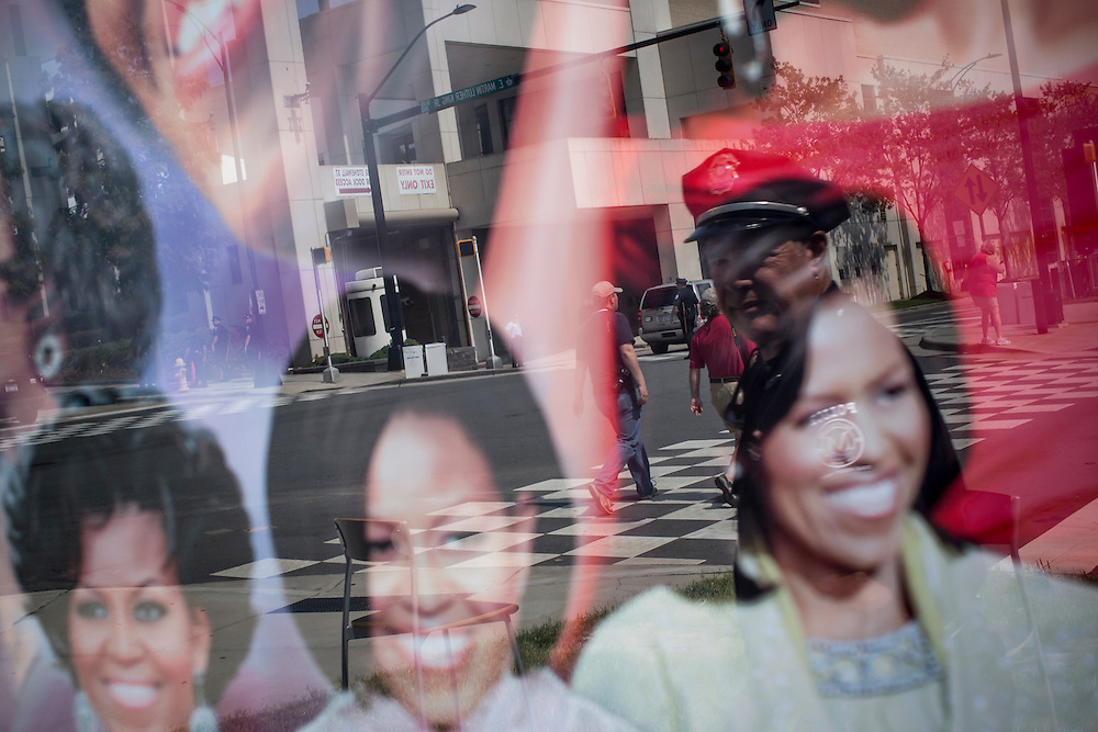 A police officer is reflected in a painting of First Lady Michelle Obama on Monday, September 3, 2012 in Charlotte, NC.