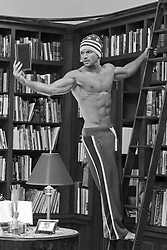 hot guy standing on a library ladder reading a book while wearing only sweatpants and a ski cap