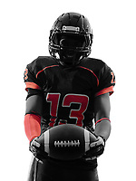 one american football player standing holding ball in silhouette shadow on white background
