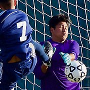 Golden West goal keeper takes on Fullerton forward Steven Garcia (7) in second half play of Golden West's 1-0 win.