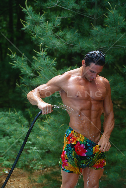 muscular man hosing his crotch  down outdoors