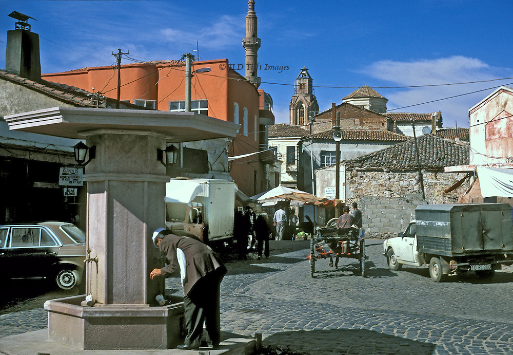 Inland town square, Ayvalik.  Man drinking at traditional fountain.  Trucks, a new car, and an old donkey cart.  Beyond, a minaret next to the remains of a domed church.