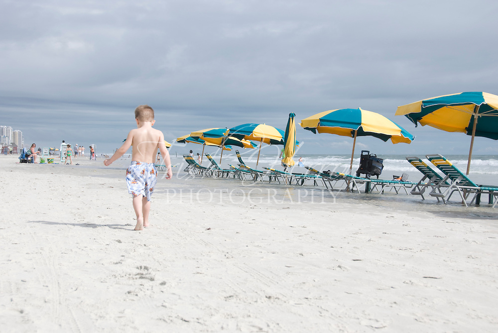 A small boy walks past a row of colorful beach umbrellas at the beach.