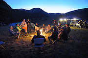Riders sit around a campfire at night after the ride