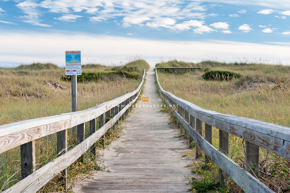 A long wooden boardwalk leads up and over the sensitive dunes to the beach at Cape Hatteras National Seashore.  Hatteras is a barrier island off the coast of North Carolina accessed via the Outer Banks Scenic Byway, NC-12.