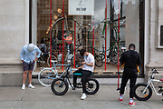 On the day that covid pandemic guidelines for shoppers in England mean that the wearing of face coverings in shops is mandatory, shoppers wearing face masks wait to enter Selfridges whose new product window is a bike shop for cycling products in the window on Oxford Street, on 24th July 2020, in London, England.