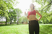 Low angle view of fit woman listening to music while holding water bottle in park