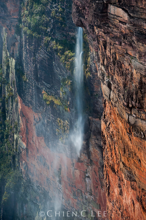 A waterfall cascades over the immense cliff of Mount Roraima, but dissipates into a fine mist before reaching the ground.