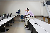 Depressed Man Sitting on Desk with Moving Box