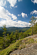 Adirondacks, NY<br /> RP344308<br /> <br /> A big system sat overhead as I climbed Baxter Mountain, a small but strategic peak.  Quite a few of the High Peaks and important drainages connect like spokes to Keene Valley, laid out below the open slabs here on the south side.  I waited for breaks from above to light the landscape, small pieces of cumulus breaking off to race across blue sky and cast shadows that ran through the valley and up mountainsides.  I was lucky for a while, but the balance tipped towards still-interesting skies but the subject mostly in shadow--not in favor of man and camera.