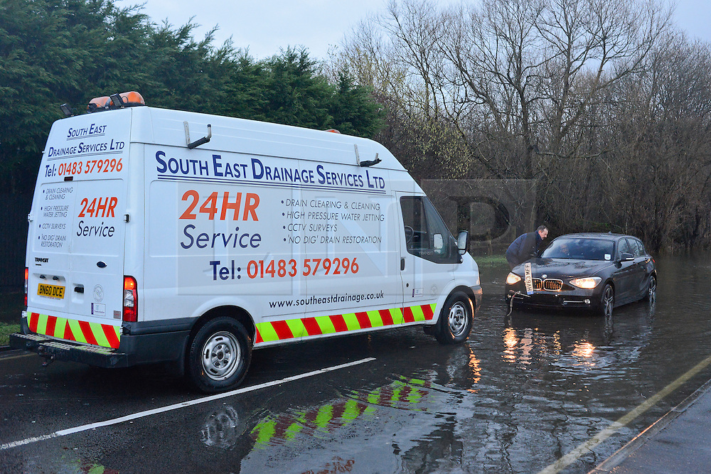 © Licensed to London News Pictures. 03/01/2014. Jacobs Well, UK A van stops to tow a broken down BMW. Cars pass through flood water created by the River Mole bursting it's banks at Jacobs Well in Surrey today 3rd January 2013. Floods an heavy rain are continuing to effect travel and people across the country today. Photo credit : Stephen Simpson/LNP