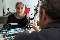"© Licensed to London News Pictures. 05/10/2018. LONDON, UK. Tom Sachs issues a passport to a visitor. Preview of ""Swiss Passport Office"" by American artist Tom Sachs at Galerie Thaddaeus Ropac in Mayfair.  To coincide with Frieze Week, the gallery will remain open for 24 hours from 6pm 5 October to 6pm 7 October for the issuing of serial-numbered Tom Sachs Swiss passports for visitors.  The installation reflects the concerns relating to Brexit, Syria and Donald Trump's immigration policies and challenges the notion of global citizenship.  Photo credit: Stephen Chung/LNP"
