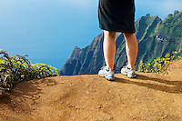Womans legs and feet standing on the Pihea Trail overlooking the Kalalau Valley and the Pacific Ocean on the Na Pali Coast of Kauai, Hawaii, USA.