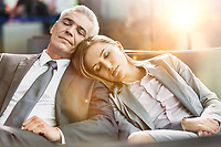 Portrait of business couple sleeping while waiting for boarding in airport with lens flare