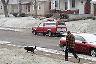 Snow falls as a man walks his dog through the Belmont area of Dayton Sunday, March 4, 2012.