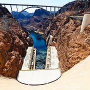Looking down from the top of the massive concrete wall of the Hoover Dam. At right is the visitor center. At the very top of frame is the Mike O'Callaghan – Pat Tillman Memorial Bridge. In the middle is the outflow of the Colorado River with the twin buildings housing the hydroelectric turbines on either side of the river. The dam spans the state border, with Arizona on the left and Nevada on the right.