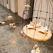 An art installation using paper, books, and a bird cage in the art gallery at the Maritime Museum of Ushuaia. The museum consists of several wings devoted to maritime history, Antarctic exploration, an art gallery, and a policy and penitentiary museum. The complex is housed in an historic prison building and uses the original cells and offices as exhibit spaces.