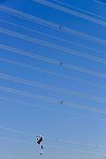 Nederland, Silvolde, 14-2-2017 Tussen Doetinchem en de Duitse grens wordt dooronderaannemer SPIE iov netwerkbehheerder Tennet een nieuwe hoogspanningsleiding aangelegd. Het gaat om een 380 kilovolt-leiding, de zwaarste spanning die we in Nederland hebben. Een medewerker van de aannemer bevstigd losse componenten aan de kabel. Hij fietst zichzelf over de kabel. De stroomdraden moeten de uitwisseling van met name groene stroom tussen Nederland en Duitsland bevorderen. Het gaat om dubbele masten van een nieuw ontwerp: iedere mast bestaat uit twee pylonen van zo'n 60 meter hoog. De nieuwe leiding loopt van hoogspanningsstation Langerak bij Doetinchem naar het Duitse Wesel, een afstand van 57 kilometer. Daarvan ligt 22,5 kilometer op Nederlands grondgebied. Foto: Flip Franssen