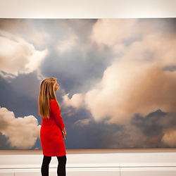 London, UK - 31 January 2013: A Sotheby's employee poses in front of a painting 1976 entitled 'Wolke (Cloud)' by Gerhard Richter (Est. £7-9 million) during the press preview of the forthcoming Sotheby's February sales of Impressionist & Modern Art and Contemporary Art in London, including works by Picasso, Bacon, Monet, Richter, Miró, Basquiat.