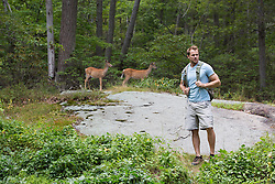 man hiking in the woods with deer