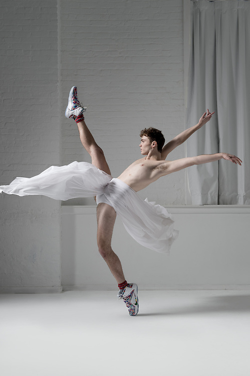 Contemporary male ballet dancer, Chase Maxwell, in the photo studio on a gray background. Photograph taken in New York City by photographer Rachel Neville.