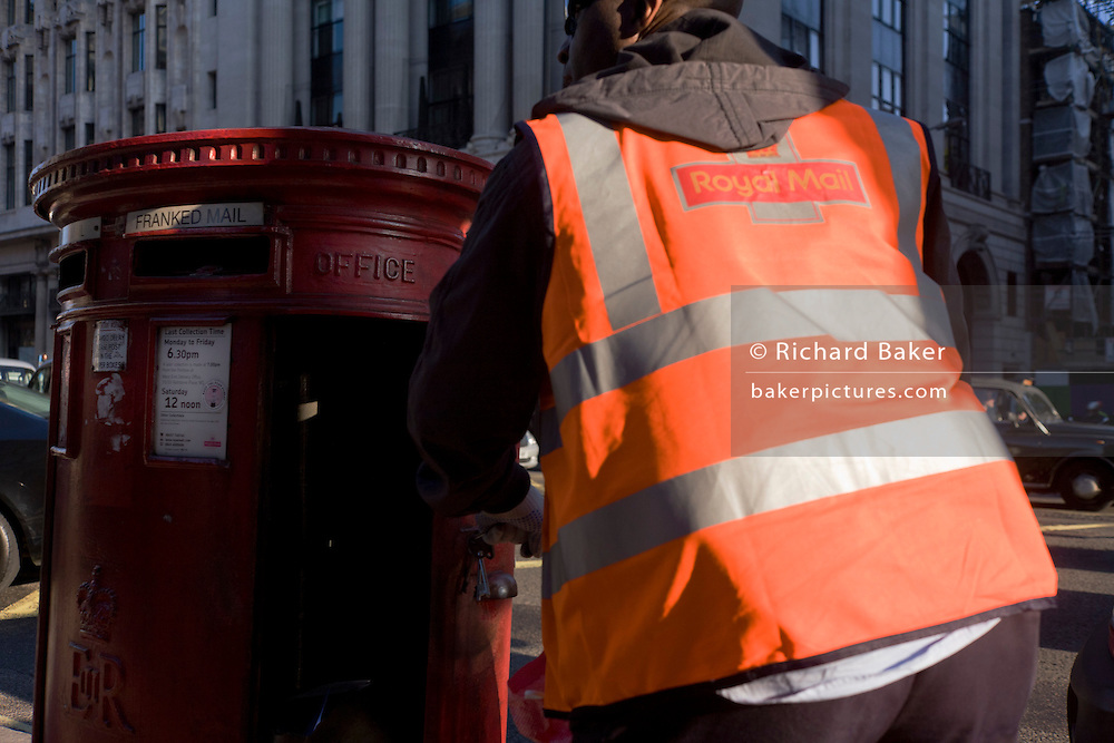 A Royal Mail postman makes a scheduled collection of post from a post box in the busy Piccadilly street in London.