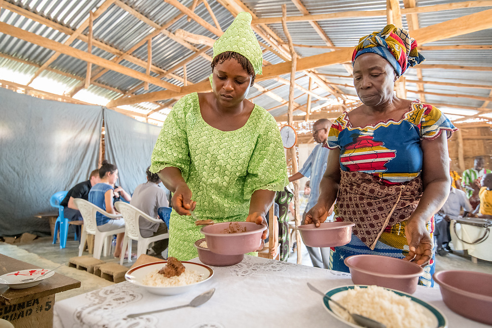 Two women in colorful dresses serve food onto plates in Ganta, Liberia.