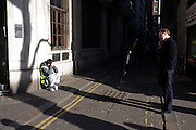 A businessman talks into his smartphone opposite a building site worker, crouching down in warm street corner sun.