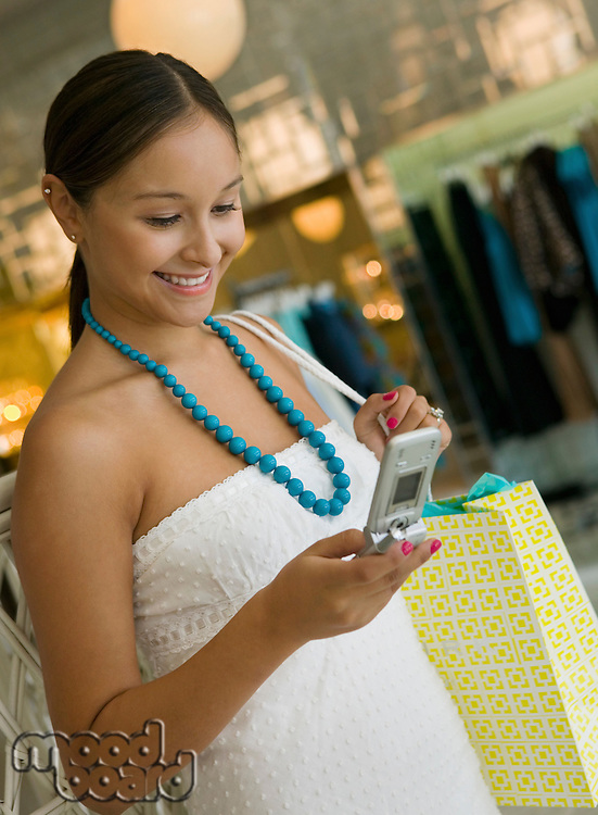 Woman Checking Cell Phone While Shopping