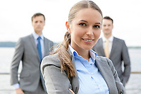 Portrait of confident businesswoman standing with coworkers on terrace
