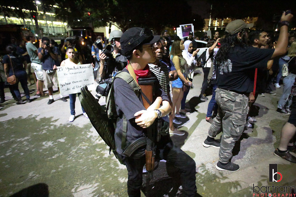 A man carries an assault rifle as protestors face off against police in Pioneer Park Cemetery following an anti white-supremacy rally at Dallas City Hall plaza on Saturday, Aug. 19, 2017. (Photo by Kevin Bartram)