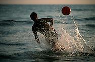 An italian plays soccer/football in the waves off  the beach in Terracina, Italy. ©2003 Brett Wilhelm/Brett Wilhelm Photography | www.brettwilhelm.com