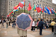 person with an American flag umbrella location Rockefeller center in New York City