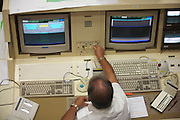 A European Space Agency technician at Ariane launch control monitors rocket systems hours before a satellite launch