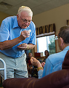 Deacon Harvey Quinette distributes Communion to nursing home residents during a prayer service. (Sam Lucero photo)