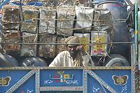 19 OCT 2001, ISLAMABAD/PAKISTAN:<br /> Mann faehrt auf der Ladeflaeche eines LKWs in Begleitung von alten Faessern und Kanistern durch die Strassen von Islamabad<br /> IMAGE: 20011019-02-048