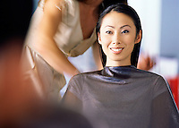 A pretty young Asian woman smiling while  having her hair done in a beauty salon.