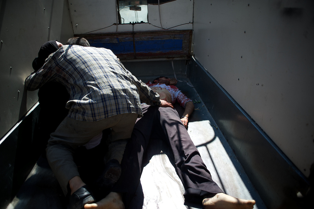 August 10, 2012 - Aleppo, Syria: A man and a woman mourn the death of their son, killed minutes earlier by heavy shelling from the Syrian Army against a bakery in the residential area of Tariq Al-Bab in central Aleppo. At least 12 people have died and more the 20 got injured during the attack...The Syrian Army have in the past week increased their attacks on residential neighborhoods where Free Syria Army rebel fights have their positions in Syria's commercial capital, Aleppo. (Paulo Nunes dos Santos/Polaris)