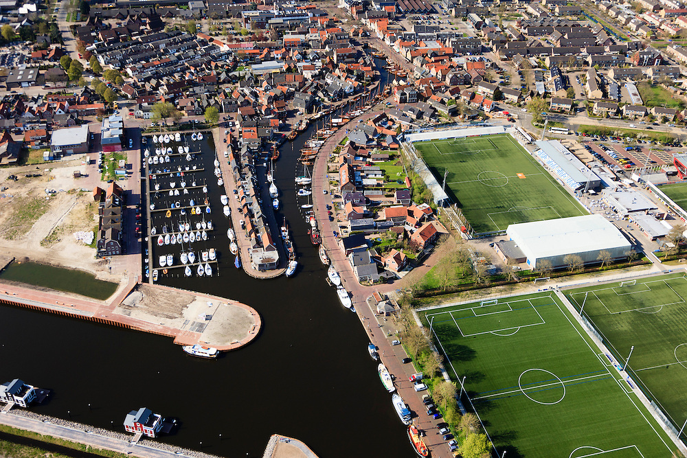Nederland, Utrecht, Bunschoten-Spakenburg, 01-05-2013;<br /> Jachthaven met aangemeerde zeilboten, nieuwbouwwijk met huizen in oude stijl en Sportpark de Westmaat,het voetbalveld en -stadion van de IJsselmeervogels aan de Westdijk.<br /> Marina with moored sailboats, new neighbourhood with old style houses and the sporting grounds Westmaat, the football field and stadium of the local football club.<br /> luchtfoto (toeslag op standard tarieven)<br /> aerial photo (additional fee required)<br /> copyright foto/photo Siebe Swart