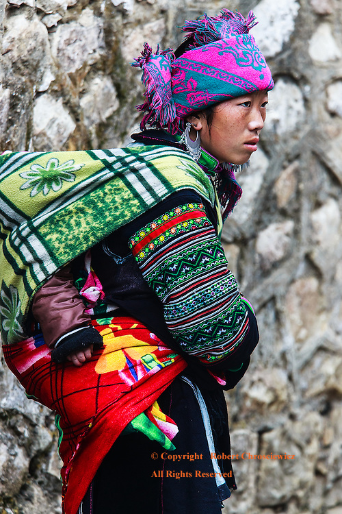 A young mother of the local hill tribe, the Hmong, pauses in stark contrast to an adjacent brick wall, carrying her young child on her back in Sapa Vietnam.